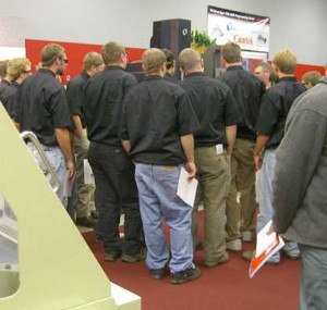 Men crowding around a booth at the Oktoberfest Tool Show