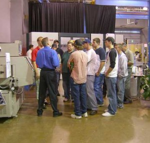 Attendees gathering around a machine tool demonstration