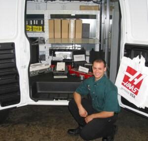 Man kneeling in front of Haas machine tool accessories