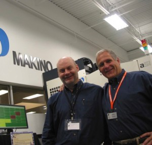 Two men smiling in front of a Makino sign
