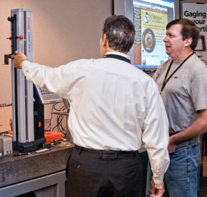 Two men watch a machine tool demonstration