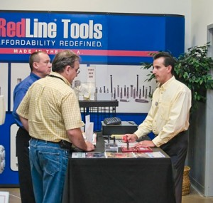 Man at RedLine Tools booth answers questions