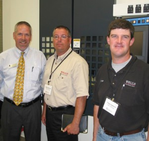 Three men standing in front of a machine tool
