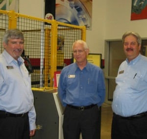 Men smiling in front of an automated machine tool