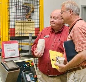 Two men examine a Roboflex machine