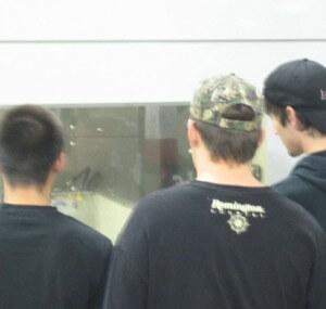 Men watching a machine through a window