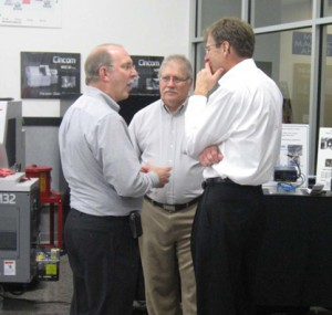 Three men in deep discussion about machine tools