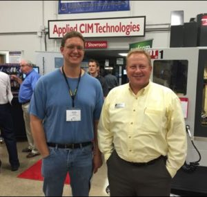 Two men smiling in front of Applied CIM Technologies booth