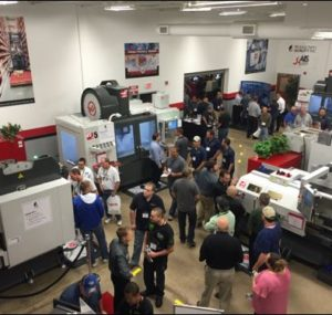Attendees discussing machine tools by the booths at Oktoberfest Tool Show